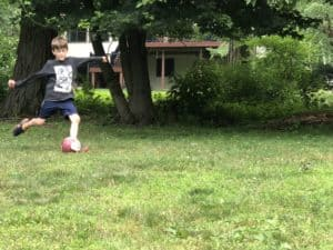 kid playing soccer in backyard