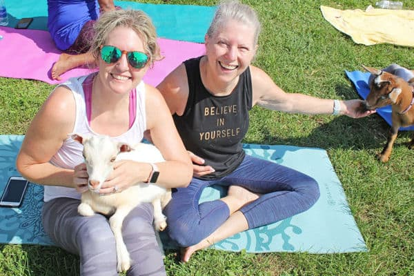 two women holding goat at yoga