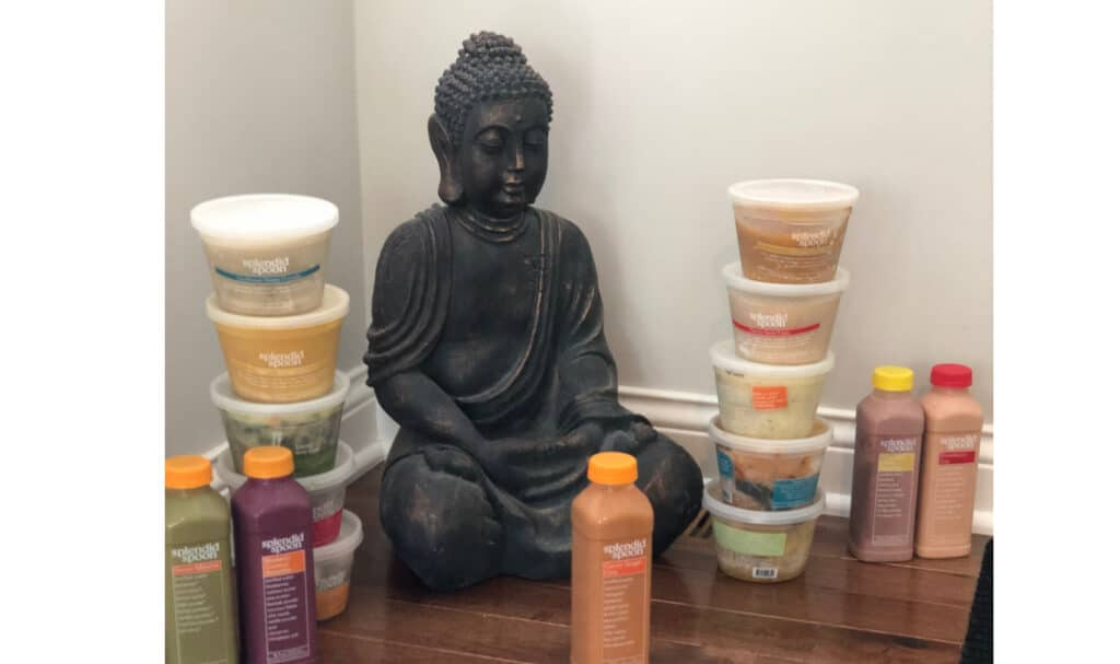 buddha statue surrounded by bowls and smoothies
